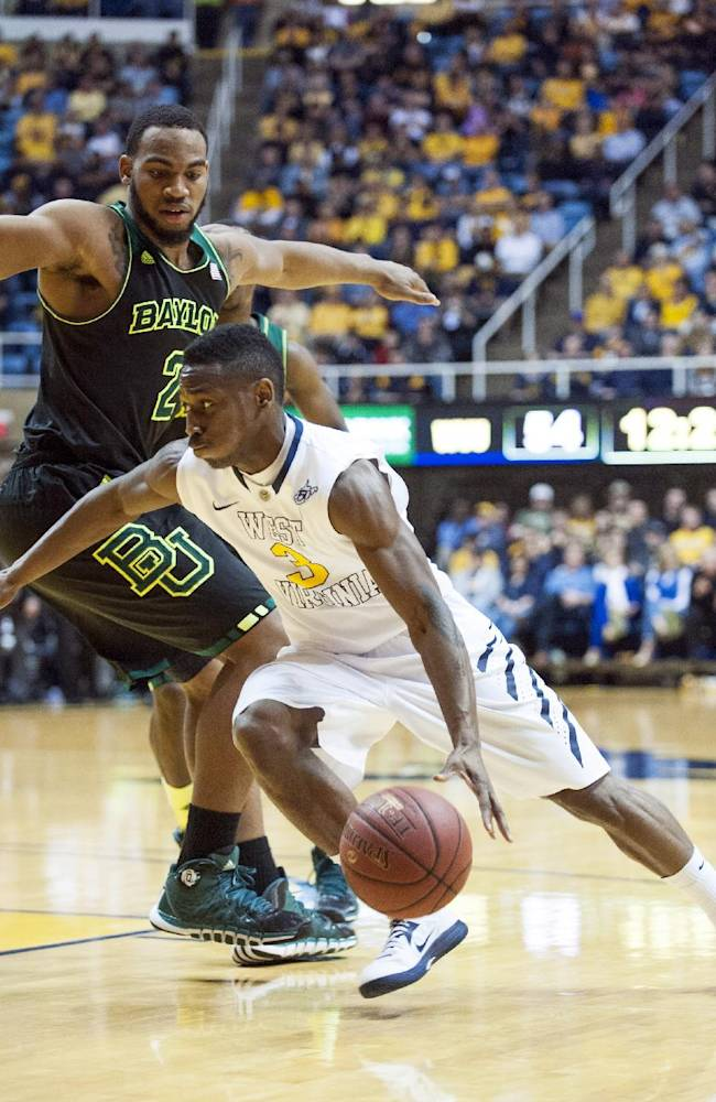 West Virginia's Juwan Staten, bottom, drives by Baylor's Rico Gathers during the second half of an NCAA college basketball game Saturday, Feb. 22, 2014, in Morgantown, W.Va. Baylor won 88-75