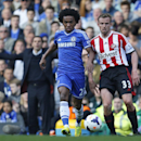 Chelsea's Willian, left, controls the ball in front of Sunderland's Lee Cattermole during their English Premier League soccer match at the Stamford Bridge ground in London, Saturday, April 19, 2014. Sunderland won the match 2-1