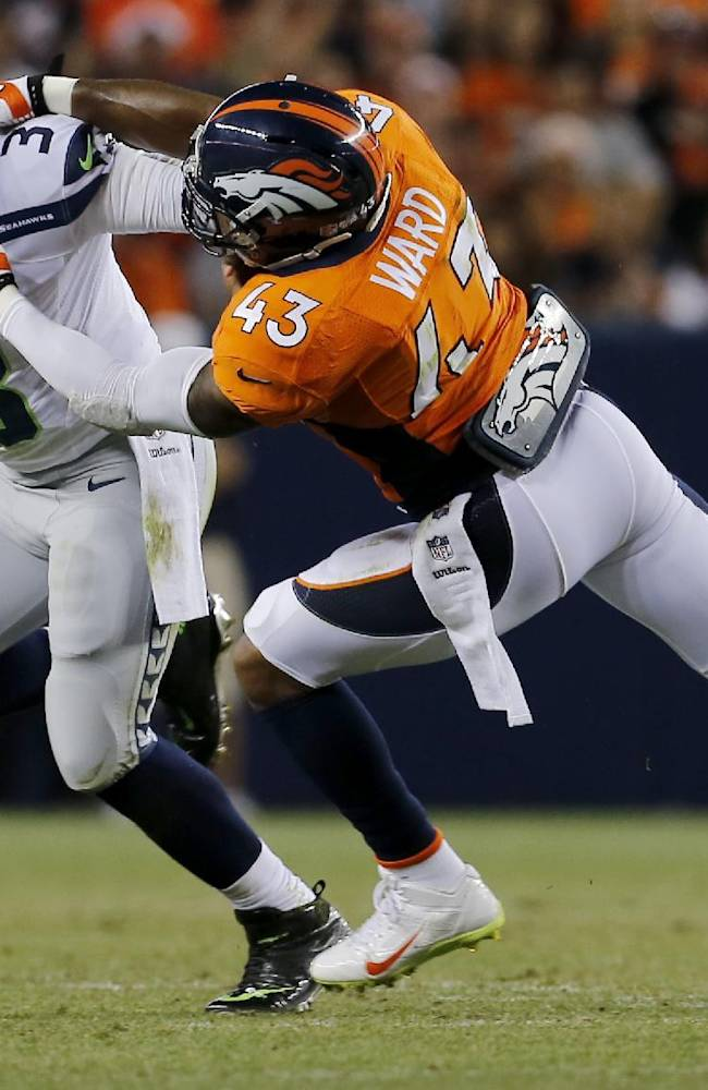 Seattle Seahawks quarterback Russell Wilson (3) has his face masked pulled by Denver Broncos strong safety T.J. Ward (43) during the first half of an NFL preseason football game, Thursday, Aug. 7, 2014, in Denver