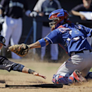 Seattle Mariners' Michael Saunders is tagged by Texas Rangers catcher Robinson Chirinos during the fourth inning of an exhibition spring training baseball game Sunday, March 9, 2014, in Peoria, Ariz The Associated Press