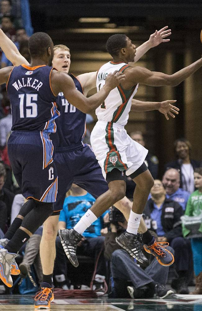Milwaukee Bucks' Brandon Knight, right, drives between Charlotte Bobcats' Cody Zeller, center, and Kemba Walker (15) during the first half of an NBA basketball game on Sunday, March 16, 2014, in Milwaukee
