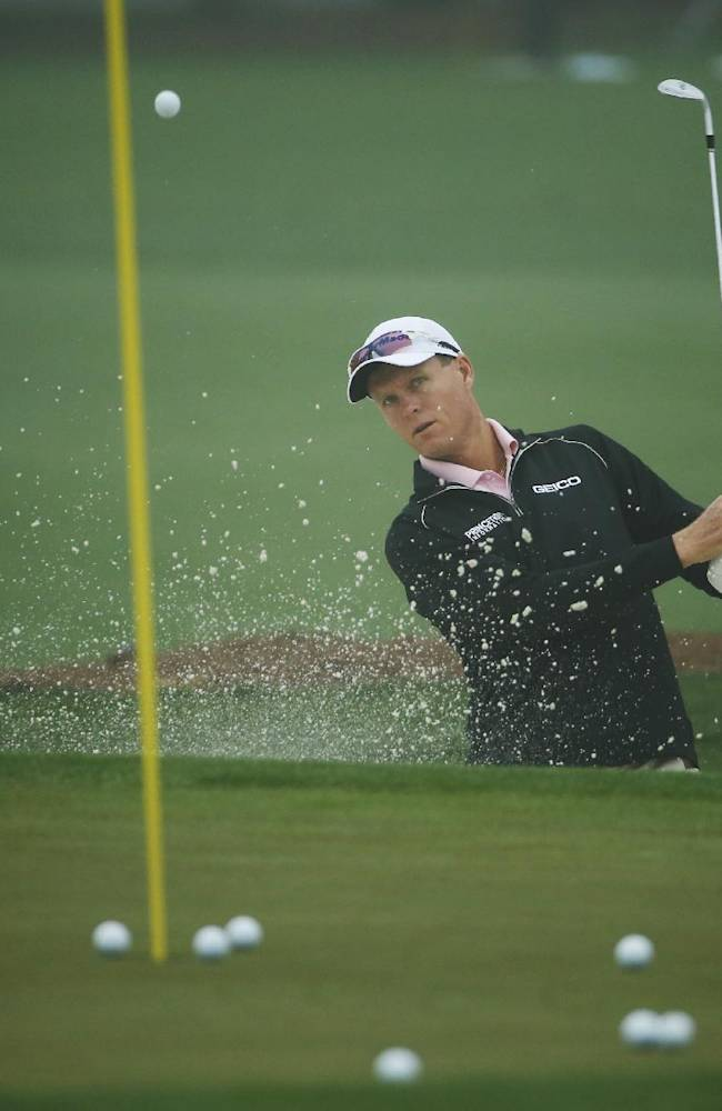 John Senden, of Australia, chips onto the practice green for the Masters golf tournament Monday, April 7, 2014, in Augusta, Ga