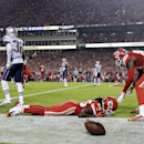 Kansas City Chiefs running back Jamaal Charles lies on the turf as he is congratulated by teammate Junior Hemingway, right, after scoring on an 8-yard touchdown pass as New England Patriots free safety Devin McCourty (32) and linebacker Jerod Mayo, left,