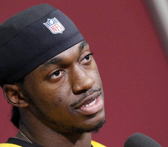 Washington Redskins quarterback Robert Griffin III, speaks during a media availability at their NFL football training facility, Wednesday, Dec. 11, 2013, in Ashburn, Va. Kirk Cousins will start for the Redskins on Sunday, and Griffin III will be the No. 3 quarterback behind Rex Grossman