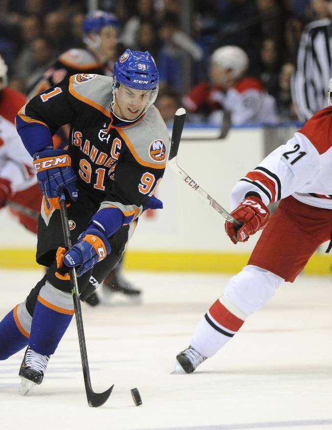 New York Islanders' John Tavares (91) drives the puck down ice away from Carolina Hurricanes' Drayson Bowman (21) Carolina Hurricanes in the second period of an NHL hockey game Saturday, Oct. 19, 2013, in Uniondale, N.Y