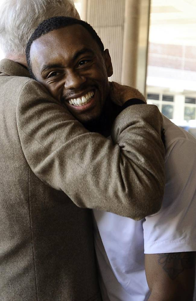 Connecticut basketball player Ryan Boatright, right, hugs former UConn men's basketball coach Dee Rowe prior to the Husky Run, Wednesday, Sept. 25, 2013, in  Storrs, Conn