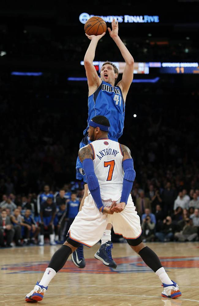 Dallas Mavericks' Dirk Nowitzki (41) shoots the game-winning basket against New York Knicks' Carmelo Anthony (7) in the final seconds of an NBA basketball game, Monday, Feb. 24, 2014, in New York.  Dallas won 110-108