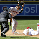 San Francisco Giants' Brandon Crawford, center, makes the late catch as Arizona Diamondbacks' Aaron Hill, right, safely steals second during the sixth inning of a baseball game on Thursday, April 3, 2014, in Phoenix The Associated Press