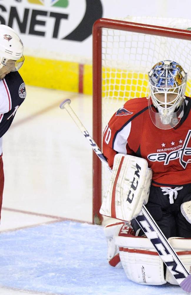 Washington Capitals goalie Braden Holtby (70) stops the puck as Columbus Blue Jackets right wing Marian Gaborik, left,  of Slovakia, looks on during the third period an NHL hockey game, Saturday, Oct. 19, 2013, in Washington. The Capitals won 4-1