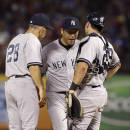 New York Yankees manager Joe Girardi (28) and catcher Francisco Cervelli, right, check on starting pitcher Hiroki Kuroda after Kurora fielded a ground out by Texas Rangers Daniel Robertson during the seventh inning of a baseball game Wednesday, July 30, 2014, in Arlington, Texas. The Ranges won 3-2. (AP Photo/LM Otero)