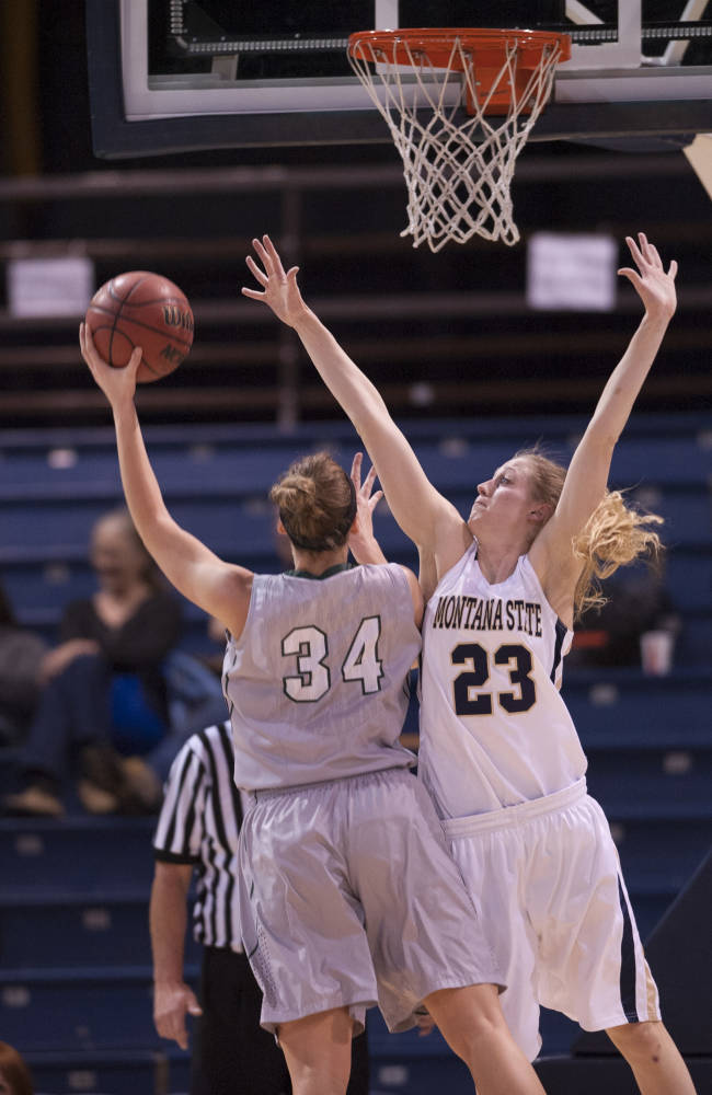 In this photo provided by Montana State University, Portland State foreword Allie Brock (34) shoots as Montana State's Ashley Brumwell (23) defends during the first half of an NCAA college basketball game on Thursday, Jan. 9, 2014, in Bozeman, Mont