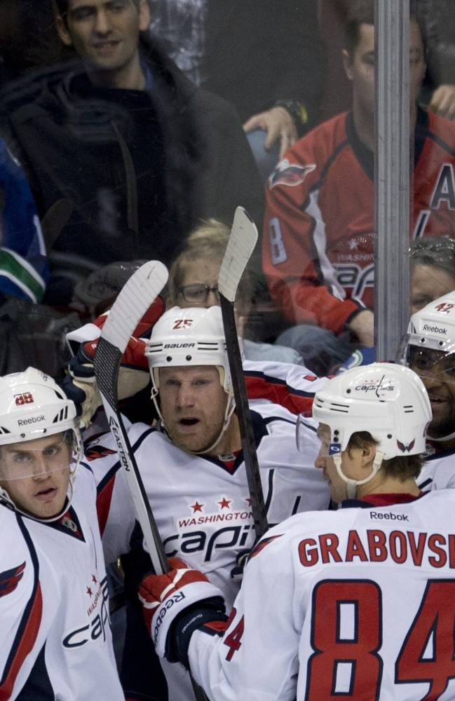 Washington Capitals left wing Jason Chimera (25) celebrates his goal with teammates Nate Schmidt (88), Mikhail Grabovski (84) and Joel Ward (42 )during the first period of NHL hockey action against the Vancouver Canucks in Vancouver, British Columbia on Monday, Oct. 28, 2013