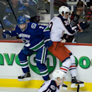 Vancouver Canucks' Dan Hamhuis, left, and Columbus Blue Jackets' Michael Chaput collide during second period NHL hockey action in Vancouver, British Columbia, Friday, Nov. 22, 2013 The Associated Press