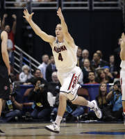 Arizona guard T.J. McConnell (4) runs to his bench after a regional semifinal NCAA college basketball tournament game as San Diego State forward Matt Shrigley (40) looks away, Thursday, March 27, 2014, in Anaheim, Calif. Arizona won 70-64. At right is Arizona guard Gabe York (1). (AP Photo/Jae C. Hong)