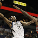 Minnesota Timberwolves forward Corey Brewer (13) goes up to the basket against Toronto Raptors forward Amir Johnson (15) in the second half of an NBA basketball game, Sunday, March 9, 2014, in Minneapolis. The Raptors won 111-104 The Associated Press