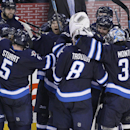 Winnipeg Jets' Blake Wheeler, center left, facing camera, celebrates with his team after scoring against the Colorado Avalanche in overtime of an NHL hockey game, Wednesday, March 19, 2014, in Winnipeg, Manitoba. The Jets won 5-4 The Associated Press