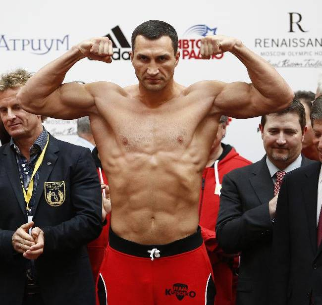 Ukrainian boxer Wladimir Klitschko, center, poses for photographers as he is weighed during the weigh-in session in Moscow, Russia, Friday, Oct. 4, 2013. Heavyweight champion Wladimir Klitschko of Ukraine will defend his WBA and IBF belts against Russia's Alexander Povetkin at the Olympic Stadium in Moscow on Saturday