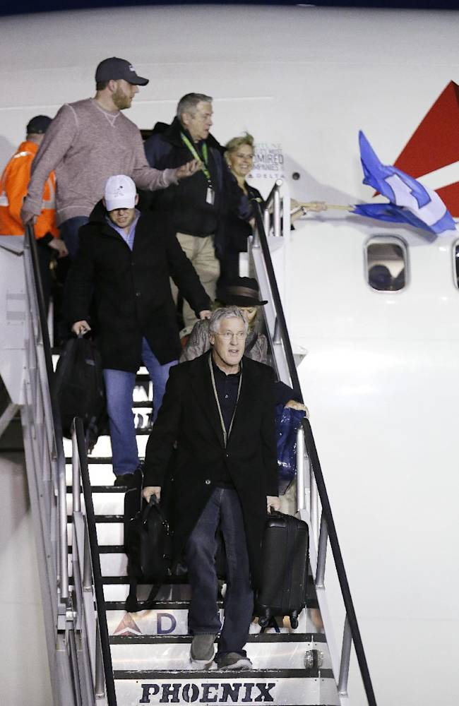 Seattle Seahawks head coach Pete Carroll, front, is followed by general manager John Schneider as he leads players and coaches off the plane upon the team's arrival Monday, Feb. 3, 2014, at Seattle-Tacoma International Airport in Seattle. The Seahawks beat the Denver Broncos 43-8 in the Super Bowl on Sunday