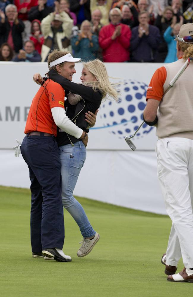 Spain's second placed Miguel Angel Jimenez, right, walks up to congratulate Joost Luiten of The Netherlands who is hugged by his girlfriend Lyan Zielhorst, right, after winning the KLM Open men's golf tournament in the beach resort of Zandvoort, western Netherlands, Sunday, Sept. 15, 2013