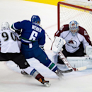 Colorado Avalanche goalie Semyon Varlamov, right, of Russia, stops Vancouver Canucks' Yannick Weber, center, of Switzerland, as Colorado's Ryan O'Reilly, left, defends during the second period of an NHL hockey game Thursday, April 10, 2014, in Vancouver,