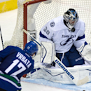 Tampa Bay Lightning goalie Ben Bishop, right, stops a shot by Vancouver Canucks' Radim Vrbata, of the Czech Republic, during the third period of an NHL hockey game Saturday, Oct. 18, 2014, in Vancouver, British Columbia The Associated Press