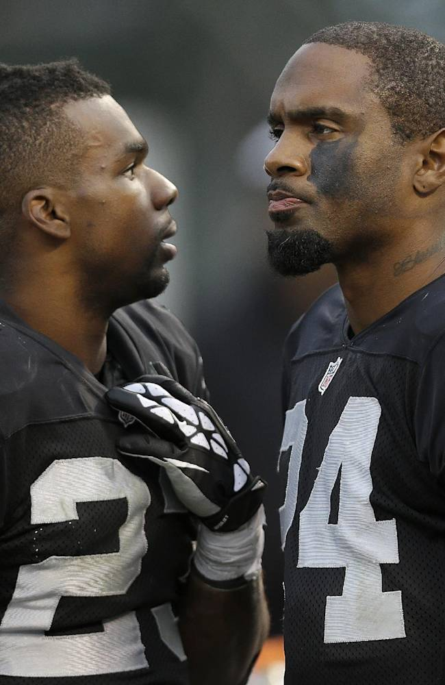Oakland Raiders cornerback Tracy Porter (23) and cornerback Charles Woodson (24) stand on the sideline during the fourth quarter of an NFL football game against the Philadelphia Eagles in Oakland, Calif., Sunday, Nov. 3, 2013