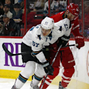 San Jose Sharks' Tommy Wingels (57) battles with Carolina Hurricanes' Riley Nash (20) during the first period of an NHL hockey game in Raleigh, N.C., Sunday, Nov. 16, 2014. Sharks won 2-0 The Associated Press