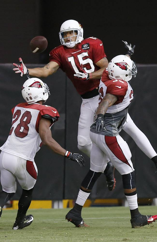 Arizona Cardinals' Justin Bethel (28) and Deone Buccanon (36) break up a pass intended for Michael Floyd (15) during NFL football training camp practice on Wednesday, July 30, 2014, in Glendale, Ariz