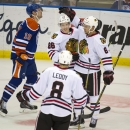 Edmonton Oilers Justin Schultz (19) skates away as Chicago Blackhawks Nick Leddy (8) and Mathieu Brisebois, right, congratulate Teuvo Teravainen for his goal during second period NHL pre-season action in Saskatoon, Saskatchewan, Sunday, Sept 28, 2014. T