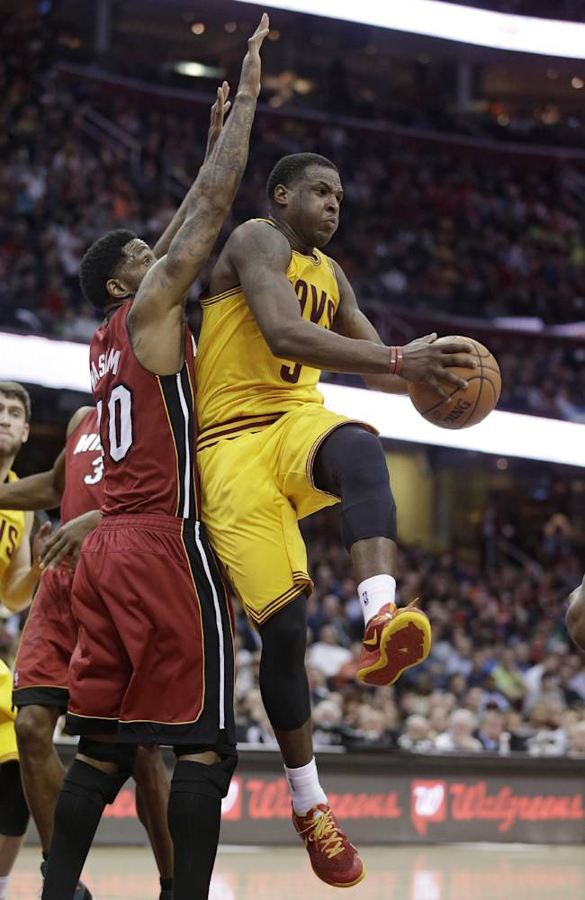 Cleveland Cavaliers' Dion Waiters, right, looks to pass to a teammate under pressure from Miami Heat's Udonis Haslem during the second quarter of an NBA basketball game Tuesday, March 18, 2014, in Cleveland