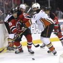 Anaheim Ducks' Kyle Palmieri, right, checks New Jersey Devils' Damon Severson during the first period of an NHL hockey game Sunday, March 29, 2015, in Newark, N.J. (AP Photo/Bill Kostroun)