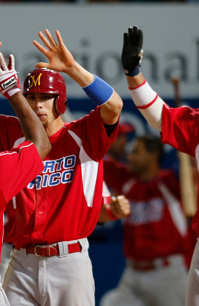 Puerto Rico's outfielder Miguel Abreu, left, is congratulated by his teammates Luis Montanes, center, and Luis Figueroa after he scoring one of the two winning runs against Venezuela during a Caribbean Series baseball semifinal game in Porlamar, Venezuela, Friday, Feb. 7, 2014. Puerto Rico will face Mexico at the final