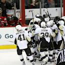 Pittsburgh Penguins players, right, celebrate after defenseman Simon Despres (47) scored to give his team a 2-1 overtime victory over the New Jersey Devils in an NHL hockey game, Friday, Jan. 30, 2015, in Newark, N.J. (AP Photo/Julio Cortez)