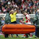 Arsenal's Jack Wilshere, center right, is substituted due to injury and shown a yellow card by referee Roger East during the Premier League soccer match between Arsenal and Hull City at the Emirates stadium in London Saturday, Oct.18, 2014