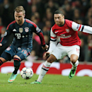 Arsenal's Alex Oxlade-Chamberlain, right, and Bayern's Mario Goetze challenge for the ball during a Champions League, round of 16, first leg soccer match between Arsenal and Bayern Munich at the Emirates stadium in London, Wednesday, Feb. 19, 2014