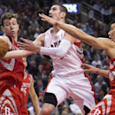 Toronto Raptors guard Nando De Colo, center, drives up the middle past Houston Rockets' Omer Asik, left, and Jeremy Lin, right, during first-half NBA basketball action in Toronto, Wednesday, April 2, 2014 The Associated Press