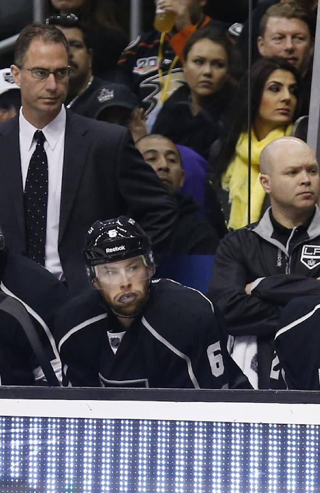Los Angeles Kings goalie Jonathan Quick, right, who is currently not playing due to illness sits on the bench as the back up goaltender to goalie Martin Jones, not pictured, next to defensemen Drew Doughty, left, and Jake Muzzin, center, during the third period of and NHL hockey game against the Anaheim Ducks in Los Angeles, Saturday, March 15, 2014. The Ducks won 2-1