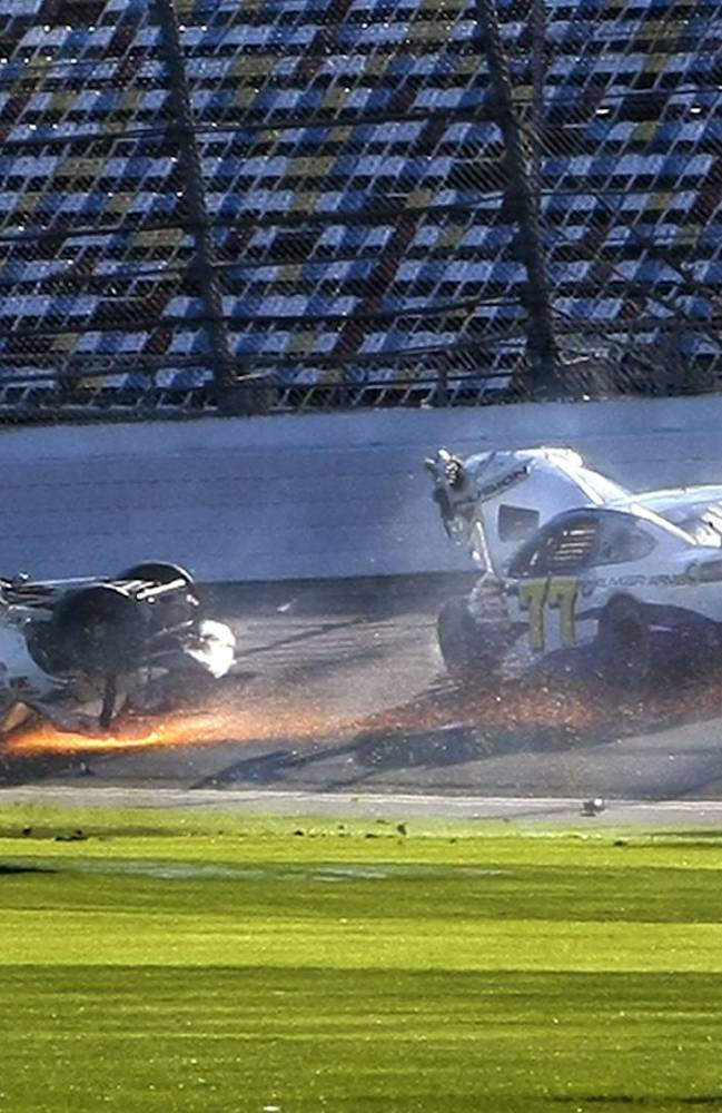 Parker Kligerman (30) slides upside down through the front stretch as Dave Blaney (77) goes around after a crash during a practice session for the NASCAR Daytona 500 auto race at Daytona International Speedway in Daytona Beach, Fla., Wednesday, Feb. 19, 2014