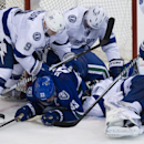 Vancouver Canucks' Henrik Sedin, of Sweden, (33) is checked by Tampa Bay Lightning's Tyler Johnson (9) and Anton Stralman, of Sweden, (6) as goalie Ben Bishop covers up the puck during the third period of an NHL hockey game in Vancouver, British Columbia