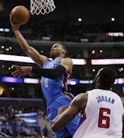 Oklahoma City Thunder guard Russell Westbrook goes to the basket as Los Angeles Clippers center DeAndre Jordan watches during the first half of an NBA basketball game in Los Angeles, Wednesday, April 9, 2014. (AP Photo/Danny Moloshok)
