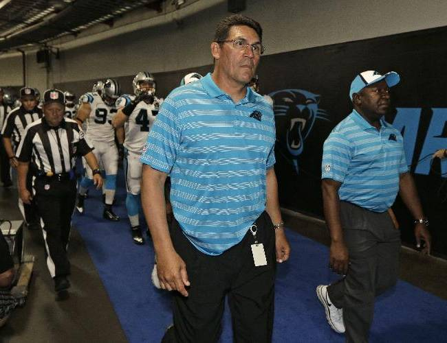 In this Aug. 8, 2014, file photo, Carolina Panthers head coach Ron Rivera leads his team from the locker room before a preseason NFL football game against the Buffalo Bills in Charlotte, N.C. Gone are the days when NFL locker rooms were a players-only domain. More coaches are making their presence felt in a place they weren't always welcomed.