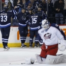 Winnipeg Jets' Dustin Byfuglien (33), Ben Chiarot (63), Chris Thorburn (22), Matt Halischuk (15) and Adam Lowry (17) celebrate after Thorburn scored on Columbus Blue Jackets goaltender Curtis McElhinney during the second period of an NHL hockey game Wedne