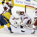 Arizona Coyotes goalie Devan Dubnyk (40) blocks a shot by Nashville Predators center Olli Jokinen (13), of Finland, in the first period of an NHL hockey game Tuesday, Oct. 21, 2014, in Nashville, Tenn. Also defending for the Coyotes are David Schlemko (6)