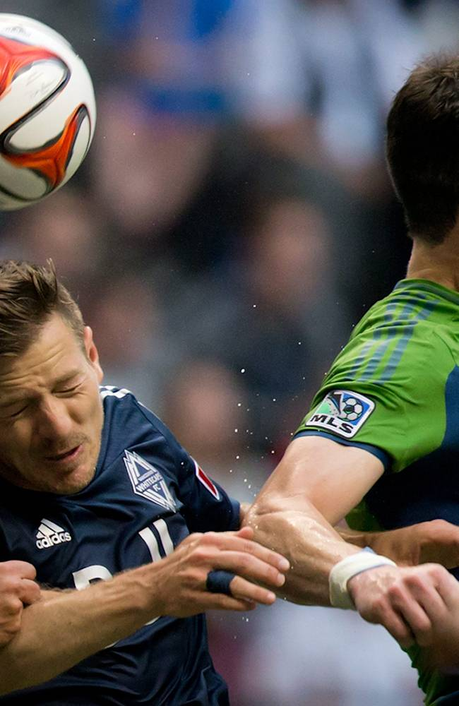 Vancouver Whitecaps' Jordan Harvey, left, and Seattle Sounders' Zach Scott vie for the ball during the first half of an MLS soccer game in Vancouver, British Columbia, on Saturday, July 5, 2014