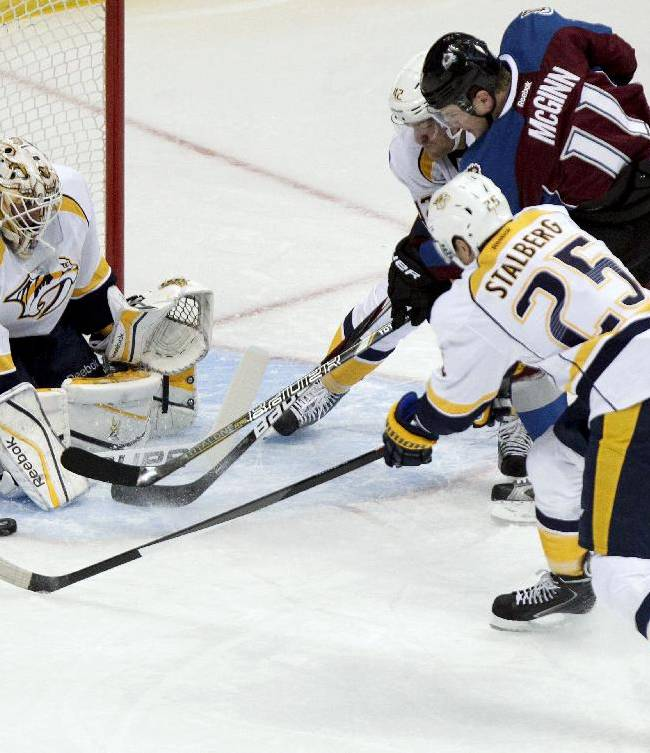 Colorado Avalanches' Jamie McGinn (11) splits defenders to make shot on goal while Nashville Predators goalie Carter Hutton (30) makes the save during the first period of an NHL hockey game Wednesday, Nov. 6, 2013, in Denver