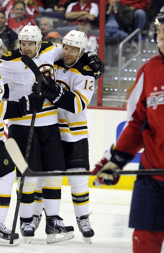 Boston Bruins right wing Jarome Iginla (12) celebrates his goal against the Washington Capitals with David Krejci (46), of the Czech Republic, and Andrej Meszaros (41) during the second period of an NHL hockey game, Saturday, March 29, 2014, in Washington