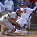 Cincinnati Reds catcher Devin Mesoraco front, catches the throw while Chicago Cubs' Ryan Sweeney slides safely into home plate on a single hit by Nate Schierholtz during the seventh inning of a baseball game in Chicago, Sunday, April 20, 2014 The Associat
