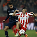 Olympiakos' Kostas Manolas, right, fights for the ball with Manchester United's Robin Van Persie during their Champions League, round of 16, first leg soccer match at Georgios Karaiskakis stadium, in Piraeus port, near Athens, on Tuesday, Feb. 25, 2014. (