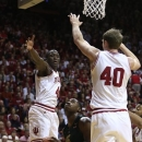 Michigan State's Derrick Nix, center, puts up a shot against Indiana's Victor Oladipo (4) and Cody Zeller (40) during the first half of an NCAA college basketball game on Sunday, Jan. 27, 2013, in Bloomington, Ind. (AP Photo/Darron Cummings)
