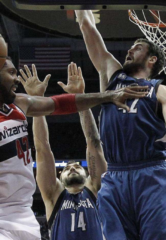Washington Wizards forward Nene (42), from Brazil, passes the ball in front of Minnesota Timberwolves center Nikola Pekovic (14), from Montenegro and forward Kevin Love (42) in the second half of an NBA basketball game Tuesday, Nov. 19, 2013, in Washington. The Wizards won 104-100